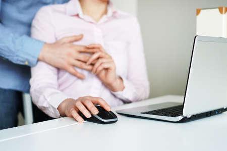 Flirt at work. Man touching secretary's breasts.
