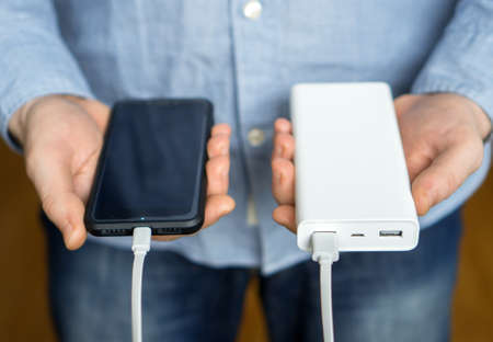 Man charging smartphone with power bank.