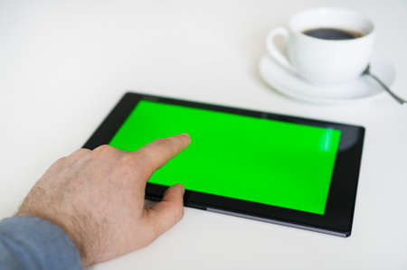 Hand touching tablet pc with green screen. Chroma key.