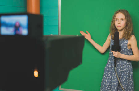 Little girl with microphone standing in front of camera on green screen. Foto de archivo