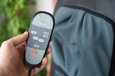Male hand holding remote control of electric massage seat.