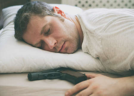Man sleeping in bed with gun near his hand.