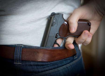 Hombre escondido arma detrás de su espalda.