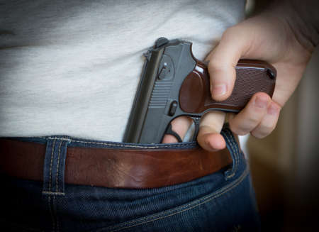 Man hiding gun behind his back. Stock Photo