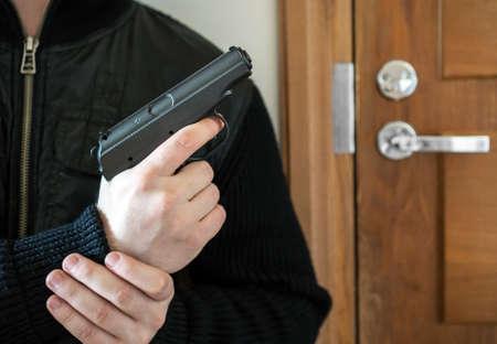 Armed man with gun waiting his victim near the door.