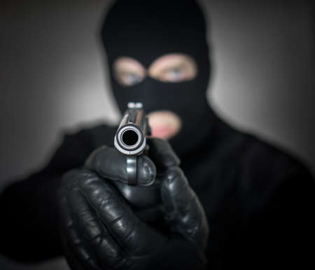 Portrait of armed man in balaclava indoors. Stock Photo