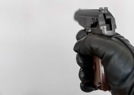 Hand in leather glove holding gun and aiming. Stock Photo