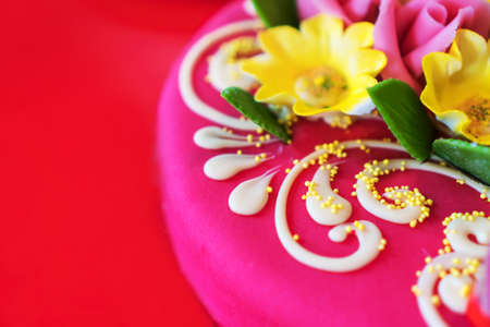 Pink marzipan cake with flowers. Space for text.