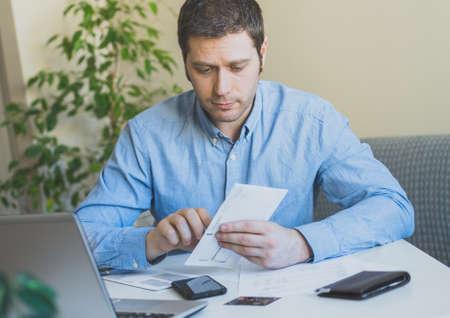 Knappe mens die zijn maandelijkse rekeningen thuis openen. Stockfoto