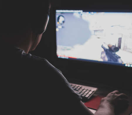 Man in headphones playing computer shooter game at night. Stock Photo