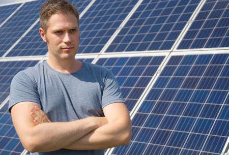 Man standing in front of solar panels. Renewable energy. Stockfoto