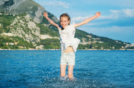 Little girl in clothes having fun in the sea. Stock Photo