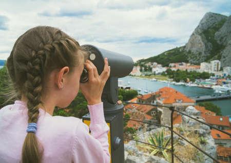 Bambina utilizzando il telescopio panoramico a gettoni.