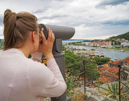 Donna che utilizza il telescopio panoramico a gettoni.
