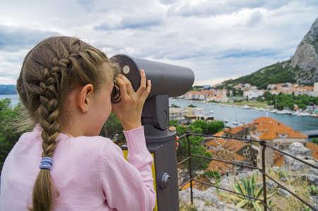 Bambina utilizzando il telescopio panoramico a gettoni. Archivio Fotografico