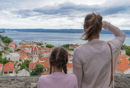 Female tourist and her daughter looking at the city.