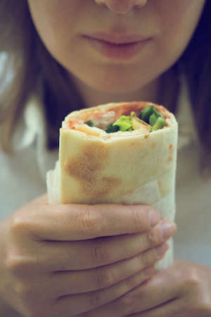 Woman holding sandwich wrap with ham, cheese and lettuce.
