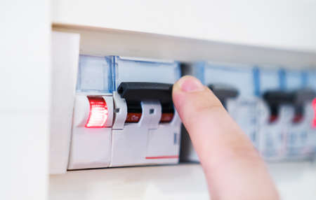 Male hand switching off fuse board. Stock Photo