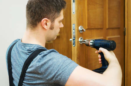 Young handyman in uniform changing door lock. Banque d'images - 114555613