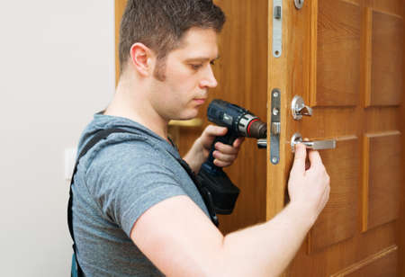 Young handyman in uniform changing door lock. Banque d'images - 114555461