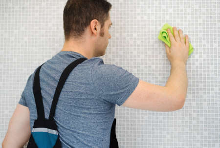 Tiler cleaning mosaic tiles in bathroom after repairs. Reklamní fotografie