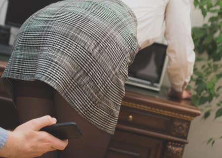 Acoso sexual en el trabajo. Hombre tomando una foto con el teléfono móvil del trasero de la secretaria.