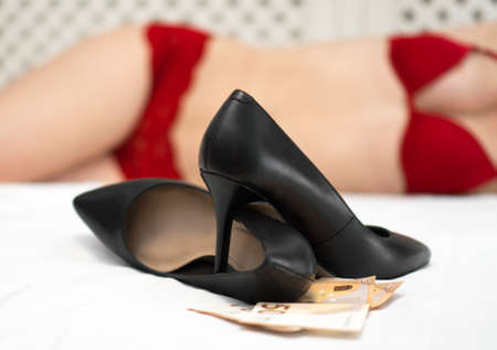 Prostitution concept. Heels, euro banknotes and woman on the bed.