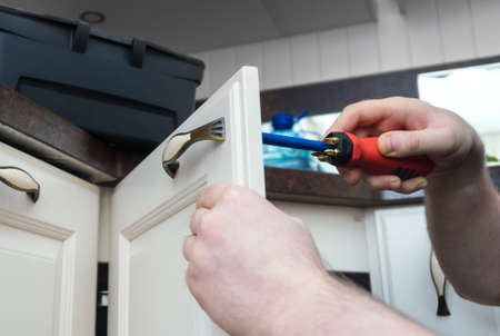 Professional handyman assembling kitchen door cabinet. 版權商用圖片