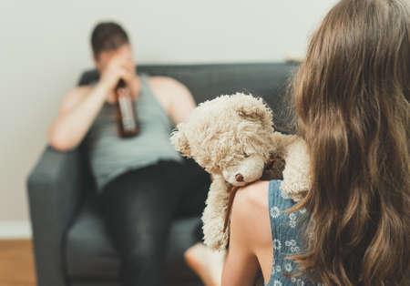 Niña con juguete de pie delante de su padre borracho. Foto de archivo