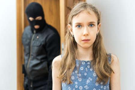 Schockiertes kleines Mädchen und wütender Räuber im Hintergrund.