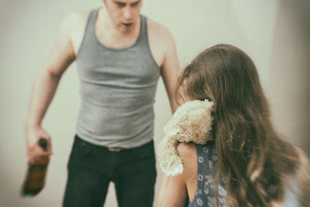 Drunk father pestering frightened little girl with toy. Stockfoto