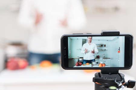Mężczyzna w kuchni kręci wideo. Koncepcja vlogowania.