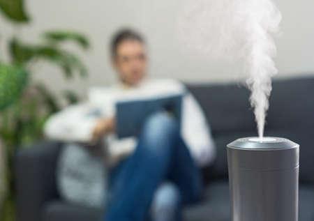 Air humidifier at living room. Man reading book