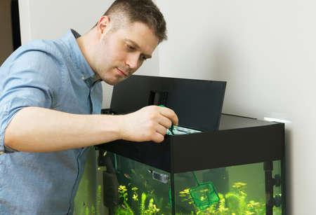 Handsome man catching fishes in the aquarium.