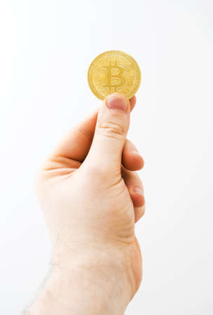 Man holding physical version of golden bitcoin on white background.