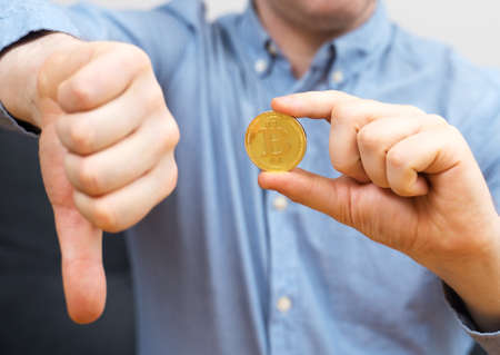 Man holding golden physical bitcoin. Investment risk. Stock Photo