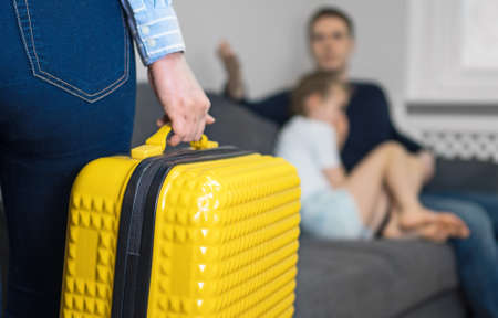 Domestic quarrel. Mother with suitcase leaving his family. Stock Photo