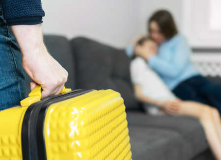 Domestic quarrel. Father with suitcase leaving his family.