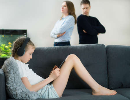 Little girl in the headphones using tablet pc while her parents in quarrel Reklamní fotografie