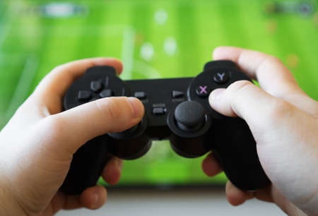 Man playing soccer video game on TV. Gamepad controller in hands.
