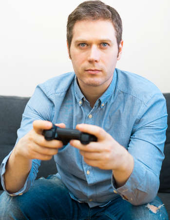 Man playing video game with gamepad in hands. Reklamní fotografie
