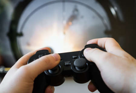 Man playing shooter video game on TV. Gamepad controller in hands.