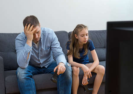 Upset father and daughter sitting on the sofa with gamepads. Reklamní fotografie