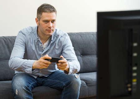 Handsome man playing video game at home. Reklamní fotografie