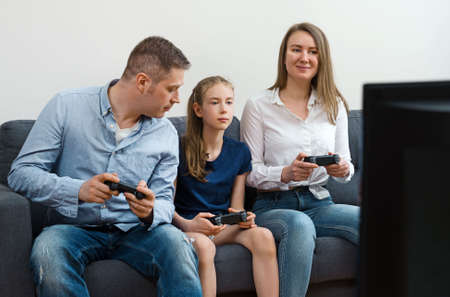 Mom, Dad and their daughter playing video game at home.