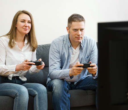 Man and woman playing video game at home.