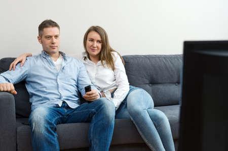 Man and woman watching TV at home.