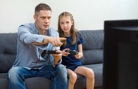 Father and daughter playing video game at home.
