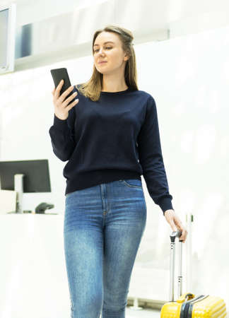 Young woman with mobile phone in front of reception.
