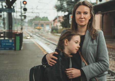 Woman with her daughter on the railway station. Travel concept. Reklamní fotografie